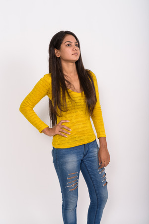 Photo for Studio shot of young Indian woman thinking while standing and po - Royalty Free Image
