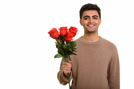 Photo for Young happy Persian man holding red roses ready for Valentines - Royalty Free Image
