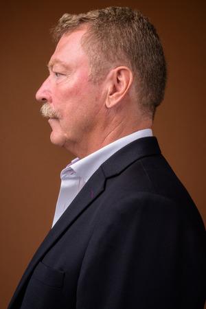Photo pour Profile view of senior businessman with mustache wearing suit - image libre de droit