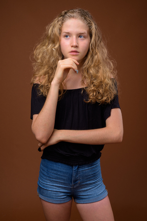 Foto de Young beautiful blonde teenage girl thinking against brown background - Imagen libre de derechos