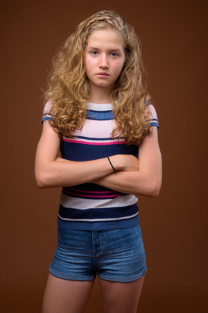 Foto de Young beautiful blonde teenage girl against brown background - Imagen libre de derechos