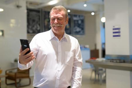 Foto de Happy senior businessman using phone at the coffee shop - Imagen libre de derechos