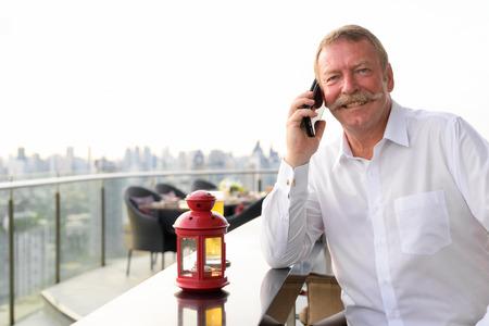 Photo pour Happy senior businessman smiling while calling with phone at the rooftop restaurant - image libre de droit