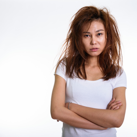 Photo for Studio shot of young Asian woman with arms crossed and messy hair - Royalty Free Image