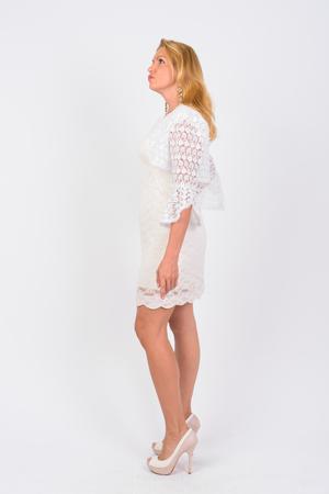 Photo pour Full body shot profile view of mature businesswoman thinking - image libre de droit