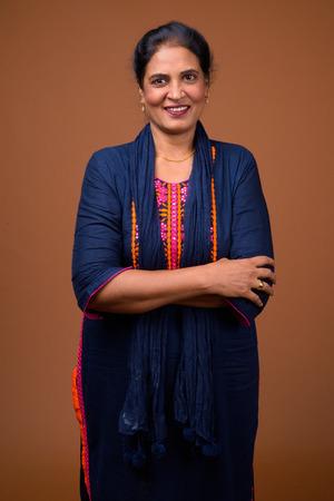 Photo pour Happy mature Indian woman smiling against brown background - image libre de droit