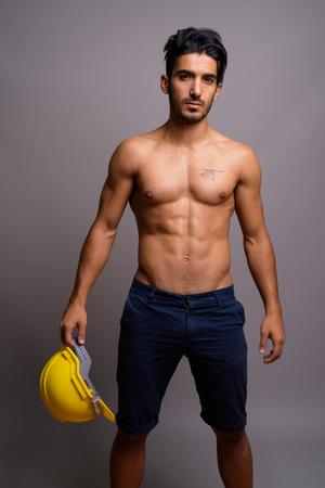 Foto de Young handsome Persian man construction worker shirtless against - Imagen libre de derechos