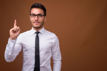 Foto de Young handsome Hispanic businessman against brown background - Imagen libre de derechos
