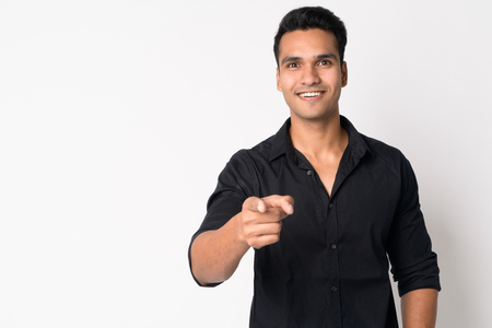 Portrait of young happy Indian businessman pointing at camera