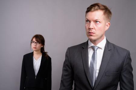 Photo pour Young businessman and young Asian businesswoman against gray bac - image libre de droit