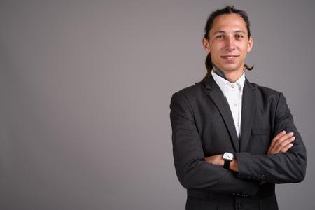 Photo pour Young businessman with dreadlocks against gray background - image libre de droit