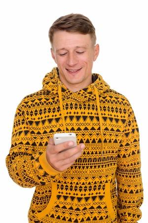 Studio shot of young happy Caucasian man using mobile phone isol