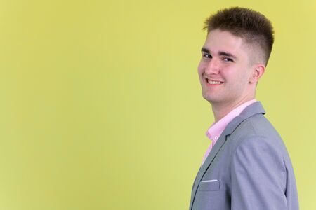 Photo for Closeup profile view of happy young businessman looking at camera - Royalty Free Image