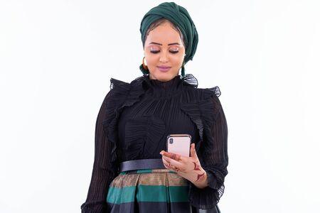 Photo pour Young beautiful African Muslim woman using phone - image libre de droit
