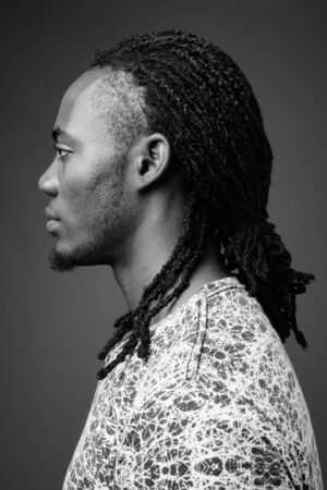 Photo pour Young handsome African man against brown background - image libre de droit