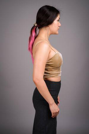 Photo pour Young beautiful Asian woman against gray background - image libre de droit