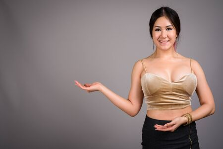 Photo for Young beautiful Asian woman against gray background - Royalty Free Image
