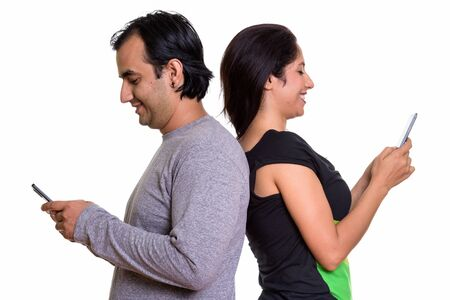 Photo pour Happy Persian couple smiling while using mobile phone together b - image libre de droit