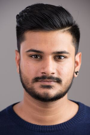 Photo pour Face of young handsome Indian man looking at camera - image libre de droit