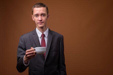 Photo pour Studio shot of young businessman against brown background - image libre de droit