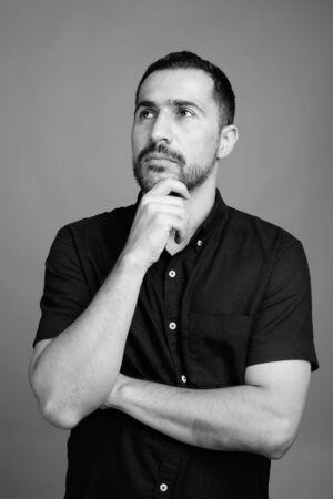 Photo pour Handsome bearded Persian man against gray background - image libre de droit