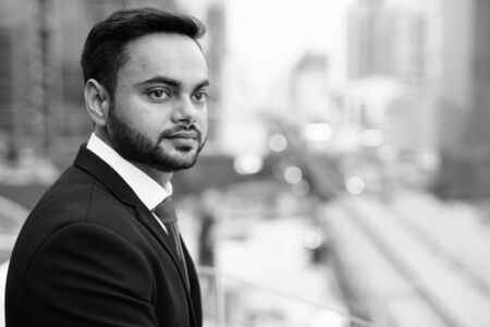 Photo for Young bearded Indian businessman against view of the city - Royalty Free Image