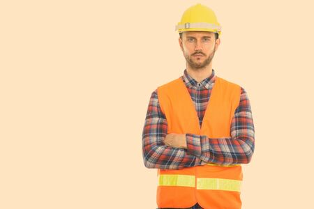 Photo pour Studio shot of young man construction worker with arms crossed - image libre de droit