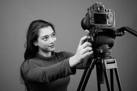 Photo pour Young beautiful Indian woman vlogging against gray background - image libre de droit
