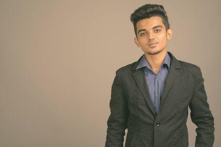 Foto de Portrait of young Indian businessman against gray background - Imagen libre de derechos