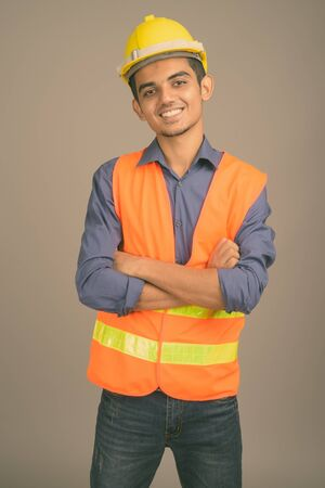 Photo for Young Indian man construction worker against gray background - Royalty Free Image