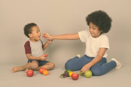 Photo for Young cute African siblings together against gray background - Royalty Free Image