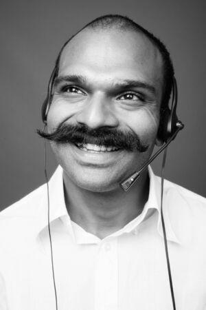Photo pour Indian businessman as call center representative against gray background - image libre de droit