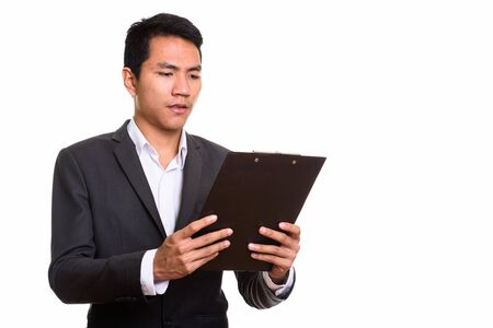 Photo for Studio shot of young Asian businessman reading on clipboard - Royalty Free Image