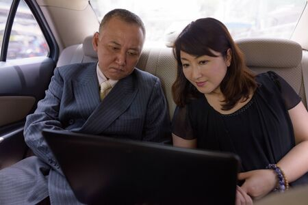 Photo for Mature Asian businessman and mature Asian woman using laptop inside car together - Royalty Free Image