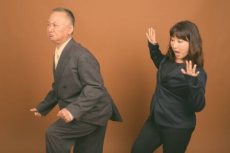 Photo pour Mature Asian businessman and mature Asian businesswoman together against brown background - image libre de droit