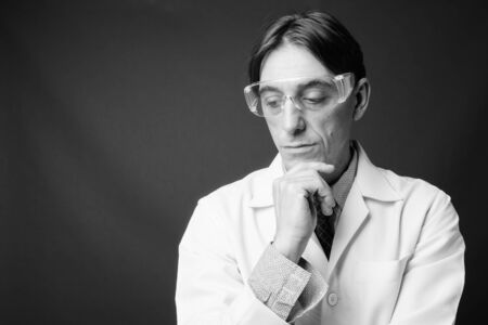 Photo pour Mature handsome Italian man doctor wearing protective glasses - image libre de droit