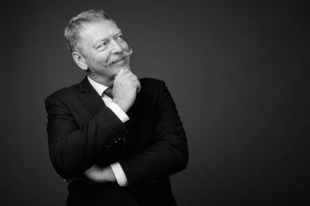 Photo pour Handsome senior businessman with mustache against gray background - image libre de droit