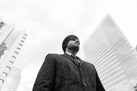 Photo pour Young handsome Indian Sikh businessman wearing turban in the city - image libre de droit