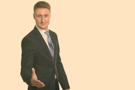 Photo pour Portrait of happy handsome businessman in suit giving handshake - image libre de droit