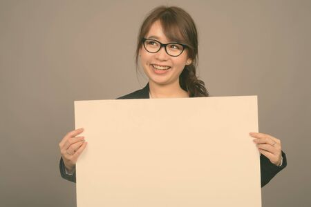 Photo for Young beautiful Asian businesswoman against gray background - Royalty Free Image
