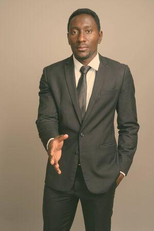 Photo pour Young handsome African businessman against gray background - image libre de droit