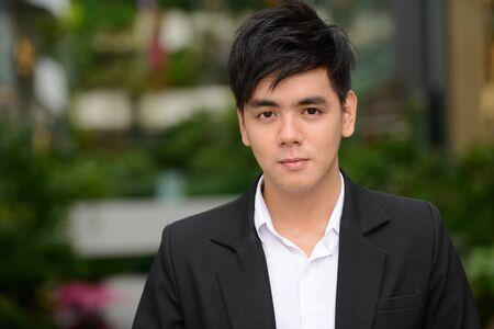 Photo pour Face of young handsome Asian businessman at the park - image libre de droit