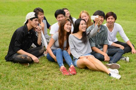 Photo pour Happy young group of friends taking selfie together at the park - image libre de droit