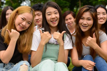 Photo for Happy young group of friends giving thumbs up together at the park - Royalty Free Image