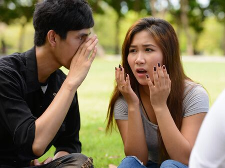 Photo pour Two young Asian friends whispering together at the park - image libre de droit