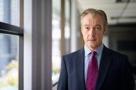 Photo pour Mature handsome businessman in suit by the window at work - image libre de droit