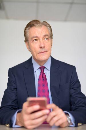 Photo pour Mature handsome businessman thinking while using phone at work - image libre de droit