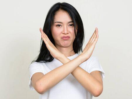 Photo pour Portrait of stressed young Asian woman showing stop gesture - image libre de droit