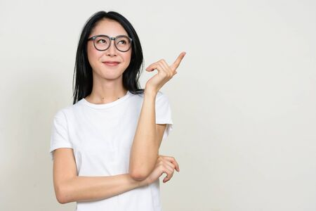 Photo pour Young beautiful Asian nerd woman thinking and pointing up - image libre de droit