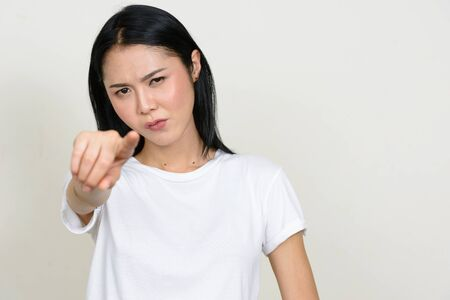 Photo pour Portrait of stressed young Asian woman pointing at camera - image libre de droit